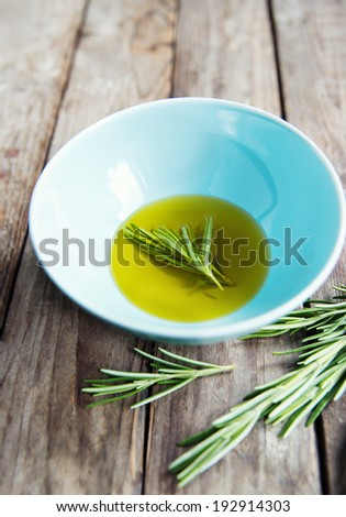 fresh rosemary bunch in a bowl with olive oil - stock photo