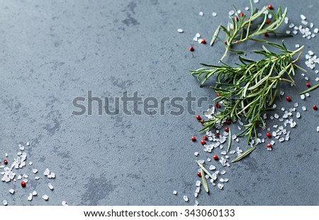 Fresh rosemary with spices on a stone background - stock photo
