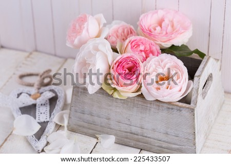 Fresh roses in box on white wooden background. Vintage style. Selective focus. - stock photo