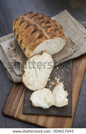 Fresh rustic loaf of bread in farmhouse setting - stock photo
