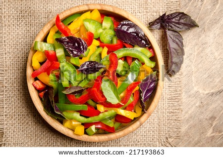 Fresh salad and fragrant multicolored pepper and basil leaves - stock photo
