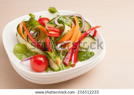 Fresh salad in plate on wooden table - stock photo