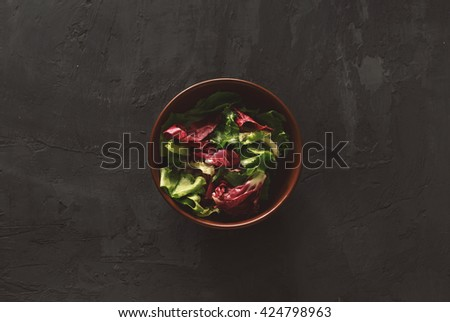 Fresh salad on a dark background, top view. Helpful and simple food - stock photo
