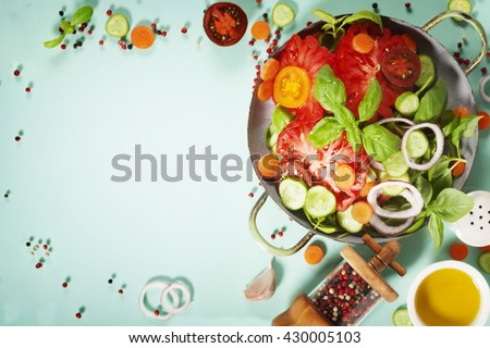 Fresh salad on blue background - Tomatoes, onion, carrot, basil, cucumbers, salt and pepper. Top view - stock photo