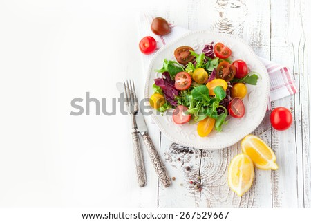 Fresh salad with cherry tomatoes, spinach, arugula, romaine and lettuce in a plate on white wooden background, top view - stock photo