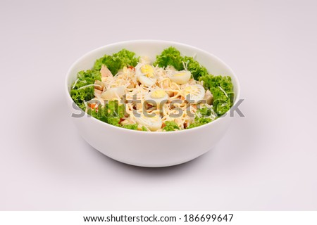 Fresh salad with chicken breast, cheese and eggs  over grey background - stock photo
