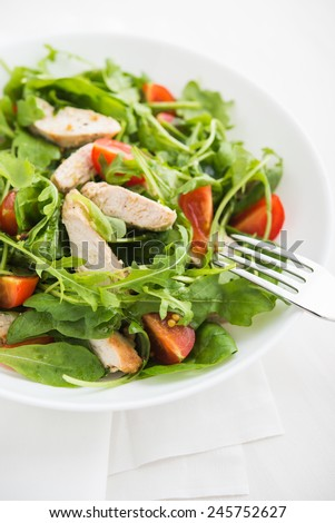 Fresh salad with chicken, tomato and greens (spinach, arugula) close up. Healthy food. - stock photo