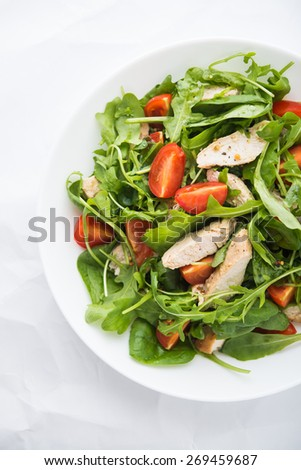Fresh salad with chicken, tomato and greens (spinach, arugula) on white background top view. Healthy food. - stock photo