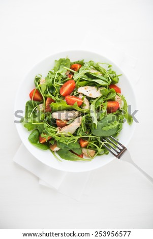 Fresh salad with chicken, tomato and greens (spinach, arugula) on white wooden background top view. Healthy food. - stock photo