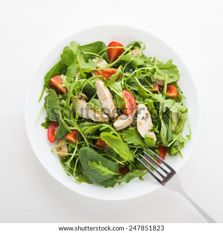 Fresh salad with chicken, tomato and greens (spinach, arugula) top view. Healthy food. - stock photo