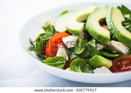 Fresh salad with chicken, tomatoes, spinach and avocado on white background close up. Healthy food. - stock photo