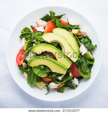 Fresh salad with chicken, tomatoes, spinach and avocado on white background top view. Healthy food. - stock photo