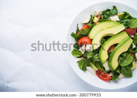 Fresh salad with chicken, tomatoes, spinach and avocado on white background top view. Healthy food. Space for text. - stock photo