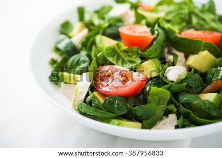 Fresh salad with chicken, tomatoes, spinach and avocado on white wooden background close up. Healthy food. - stock photo