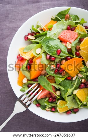 Fresh salad with fruits and greens on dark background top view. Healthy food. - stock photo