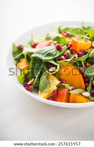Fresh salad with fruits and greens on white background close up. Healthy food. - stock photo