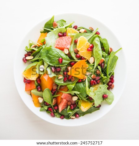 Fresh salad with fruits and greens on white background top view. Healthy food. - stock photo