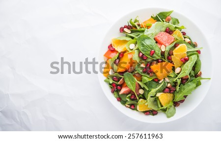 Fresh salad with fruits and greens on white background top view with space for text. Healthy food. - stock photo