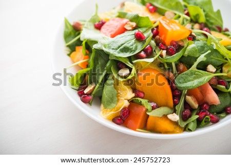 Fresh salad with fruits and greens on white wooden background close up. Healthy food. - stock photo