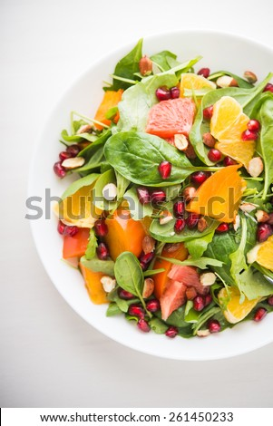 Fresh salad with fruits and greens on white wooden background top view. Healthy food. - stock photo