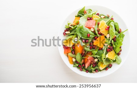 Fresh salad with fruits and greens on white wooden background top view with space for text. Healthy food. - stock photo