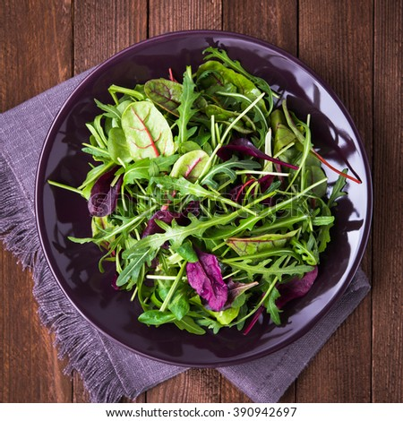 Fresh salad with mixed greens (arugula, mesclun, mache) on dark wooden background top view. Healthy food. - stock photo