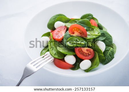 Fresh salad with mozzarella cheese, tomato and spinach on white paper background close up. Healthy food. - stock photo