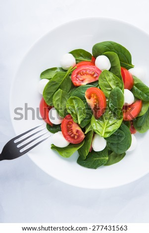 Fresh salad with mozzarella cheese, tomato and spinach on white textured background top view. Healthy food. - stock photo