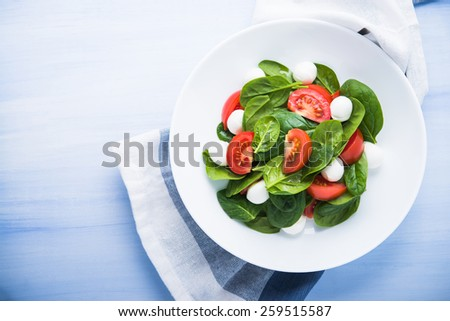 Fresh salad with mozzarella cheese, tomatoes and spinach on blue wooden background top view. Healthy food. - stock photo