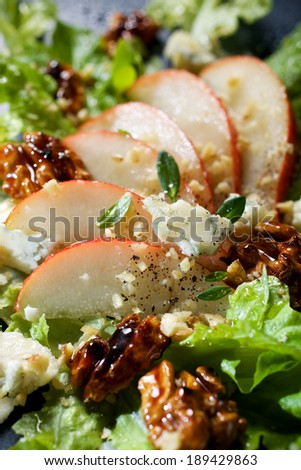 Fresh salad with pear, blue cheese and caramelized walnuts - stock photo