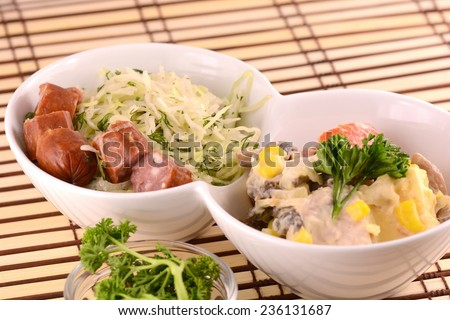fresh salad with sausage on white plate - stock photo