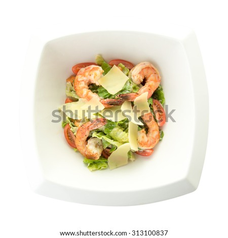 Fresh salad with shrimp and parmesan cheese on square plate isolated on white background - stock photo