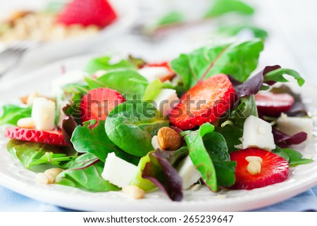 Fresh salad with strawberries, spinach leaves and feta cheese on white wooden background, selective focus - stock photo