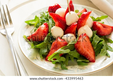 Fresh salad with strawberry, arugula and mozzarella on white plate - stock photo