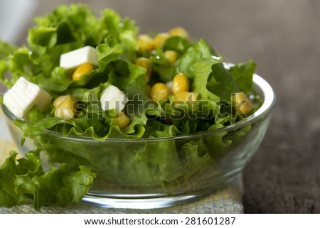 Fresh salad with sweetcorn and cheese in bowl over wood background - stock photo