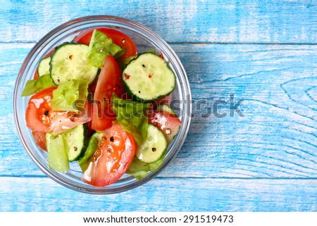 Fresh salad with tomatoes, cucumbers and lettuce - stock photo