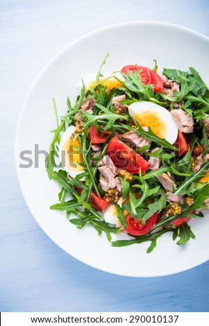 Fresh salad with tuna, tomatoes, eggs, arugula and mustard on blue wooden background top view. Healthy food. - stock photo
