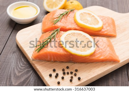 Fresh salmon and lemon on the wooden table.  - stock photo