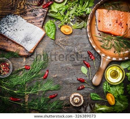 Fresh salmon fillet with ingredients for tasty cooking on rustic wooden background, top view, frame. Healthy food concept. - stock photo