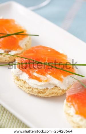 fresh salmon mini sandwich on white plate. shallow dof - stock photo