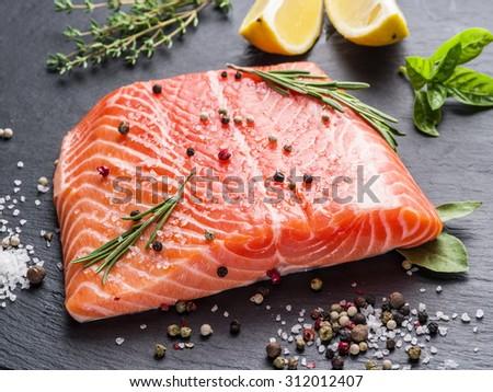 Fresh salmon on the black cutting board. - stock photo