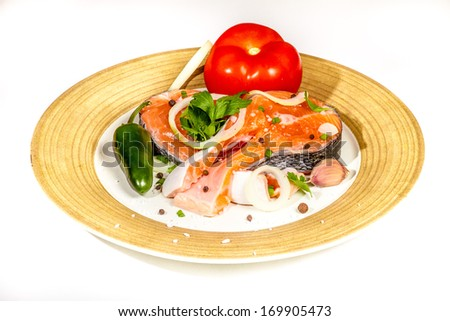 Fresh salmon steak fillets garnished with vegetables on a plate - stock photo