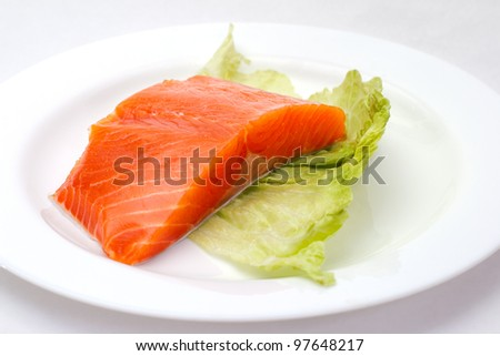 Fresh salmon steak on white plate with lemon and green salad - stock photo