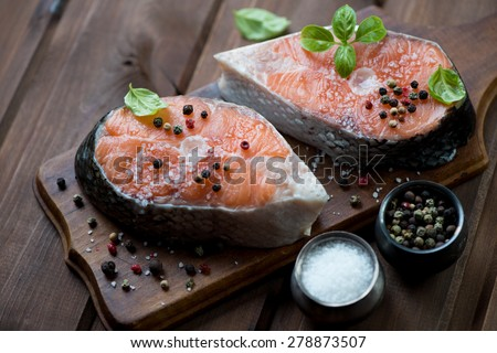 Fresh salmon steaks with seasonings, rustic wooden background - stock photo