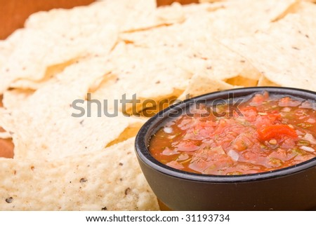 fresh salsa in a black bowl and corn chips - stock photo