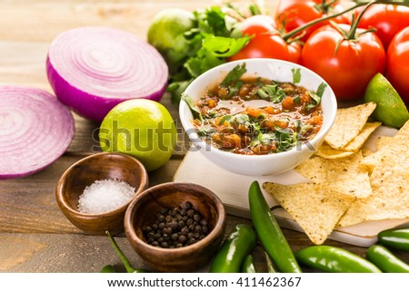 Fresh salsa in white bowl with ingredients. - stock photo