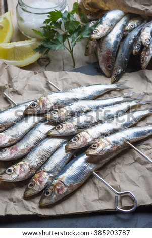 fresh sardines raw fish with coarse salt and thyme on brown pape - stock photo