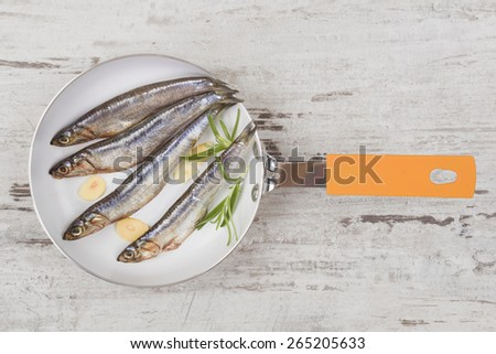 Fresh sardines with garlic and fresh herbs on pan on white wooden background, top view. Culinary healthy seafood eating.  - stock photo