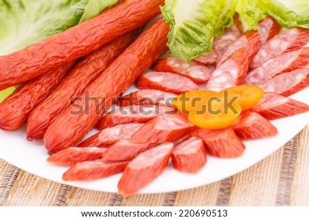 Fresh sausages and green salad leaves in plate on bamboo mat background. - stock photo