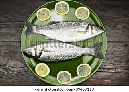 Fresh sea bass in a green plate, on a wooden surface. - stock photo